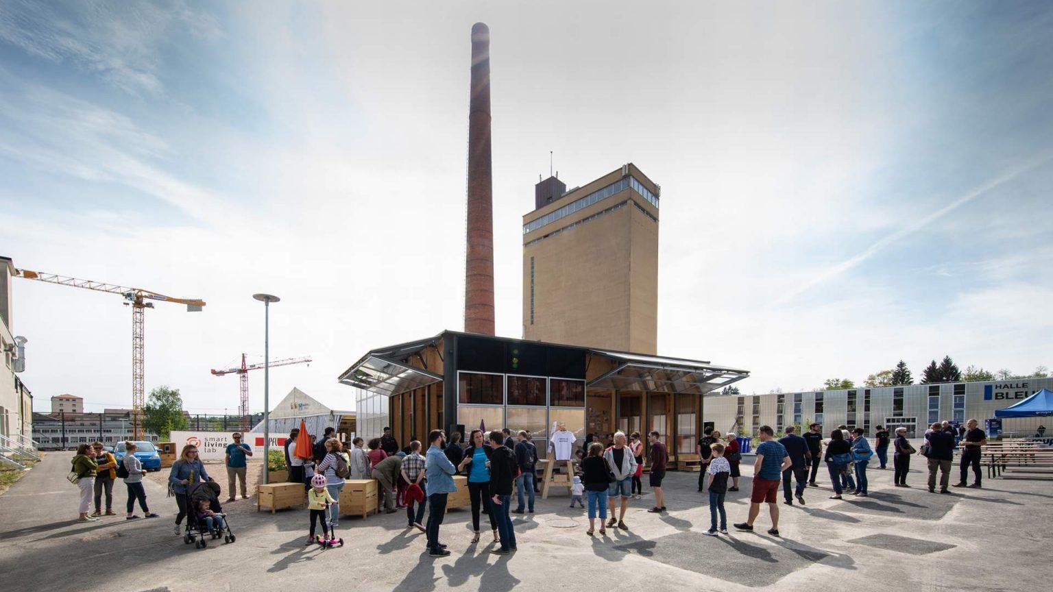 Portes ouvertes au Smart Living Lab. Des gens debout devant la Halle Bleue, à Fribourg. En arrière-plan, la cheminée de la Blue Factory