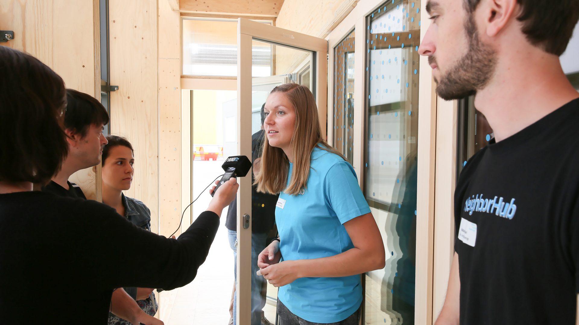 Une édutiante interviewée par une radio lors de la Conférence de presse NeighborHub Swiss Living Challenge. Blue Factory, Fribourg