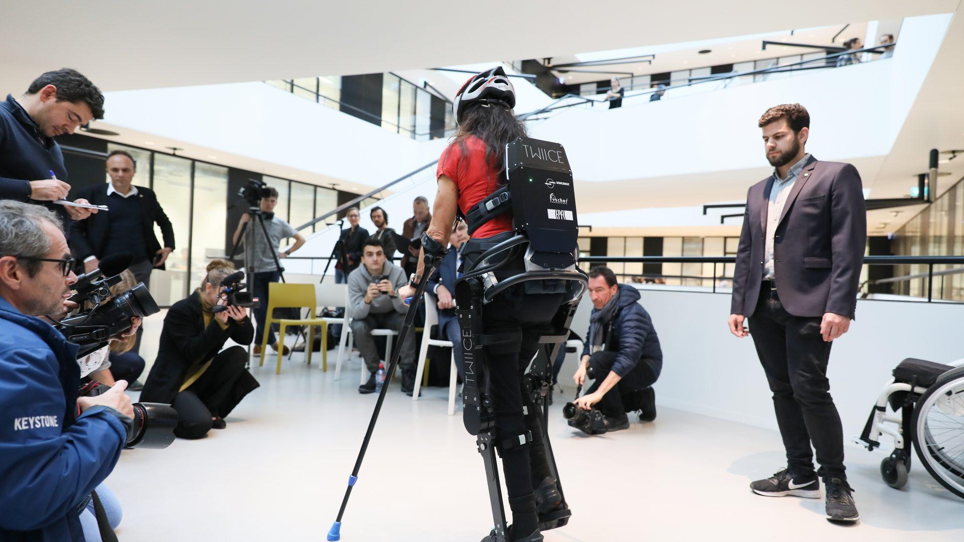 Au premier plan, Silke Pan teste le nouvel exosquelette TWIICE. Au second plan, plusieurs journalistes la filment.