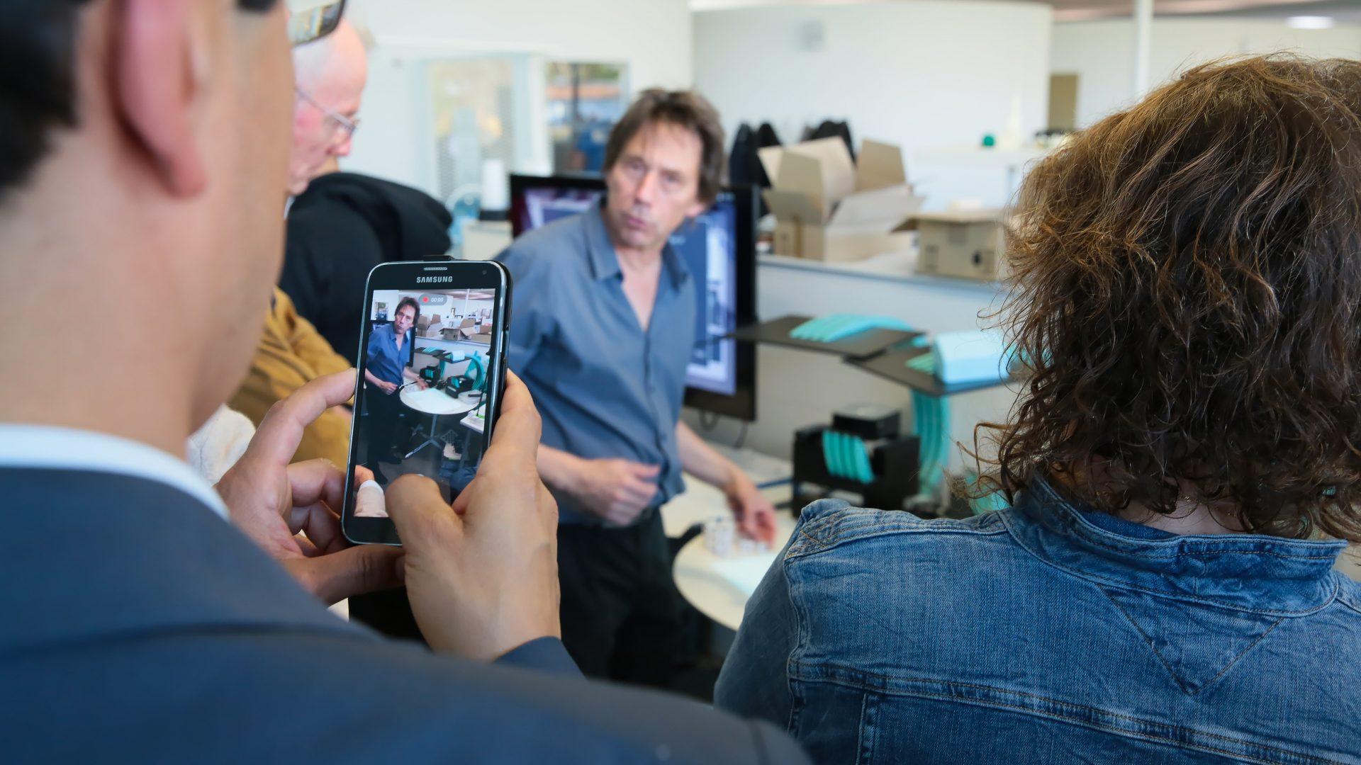 Visite des EPFL Alumni au laboratoire d'ergonomie éducative (CHILI) du prof. Pierre Dillenbourg. Au premier plan, une personne prend des photos avec un smartphone.