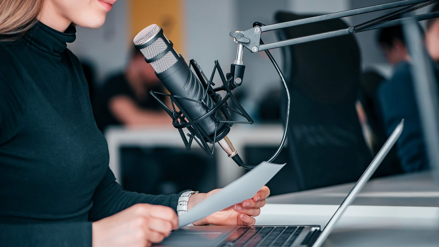 Une personne face à un micro enregistrant un podcast © iStock