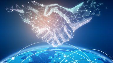 Deux mains réalisées avec constellations se serrant au-dessus d'un globe terreste bleu, sur lquel on devine un réseau