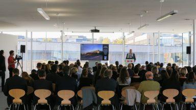 Un parterre d'invités, de dos, assis sur des chaises. Un écran affiche une image de l'ArtLab. Au fond à droite, un orateur debout derrière un podium.