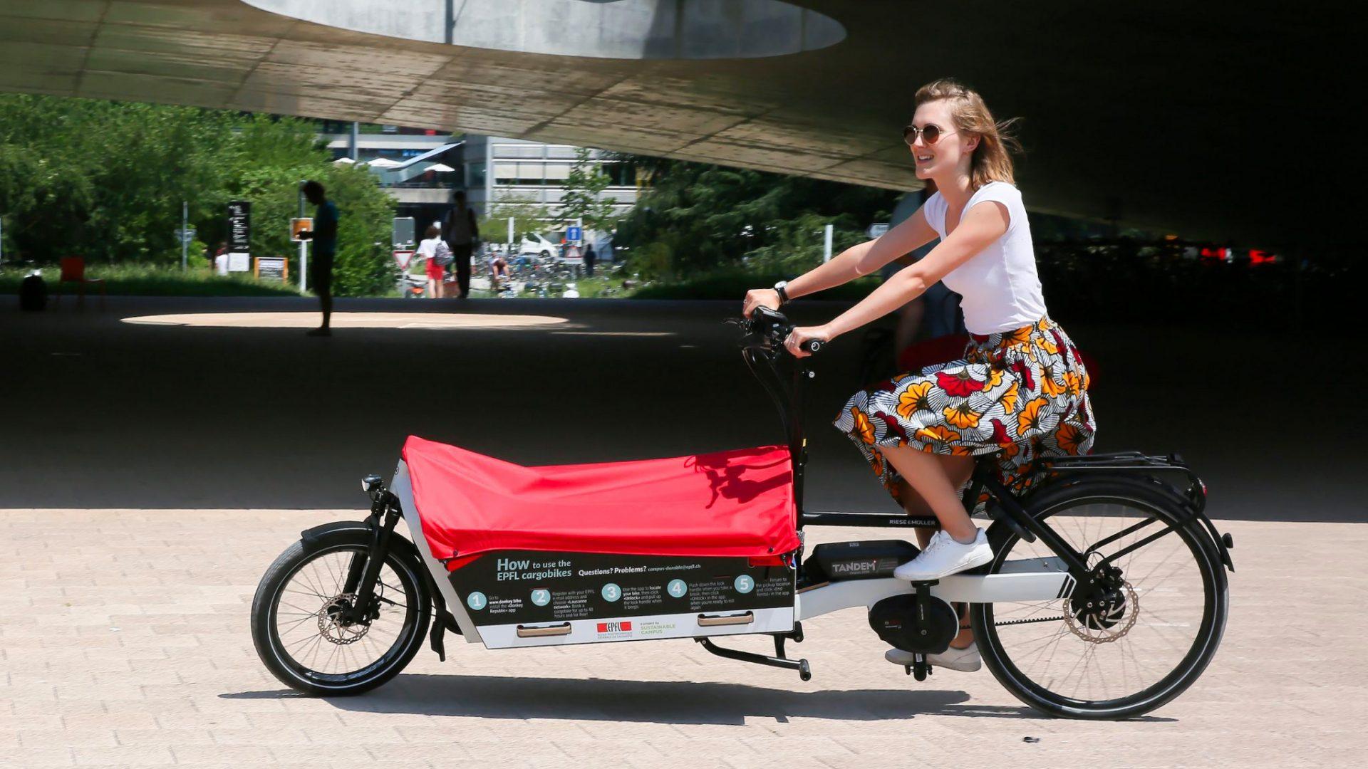 Un vélo-cargo sous le Rolex Learning Center