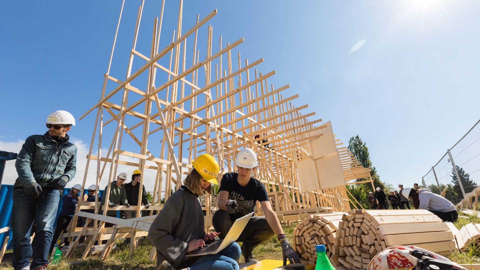La construction House 2. Des étudiants en premier plan avec des casques de chantier, consultant un ordinateur