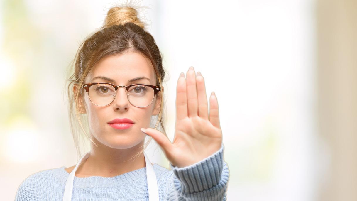 Une femme, de face, faisant une signe de refus
