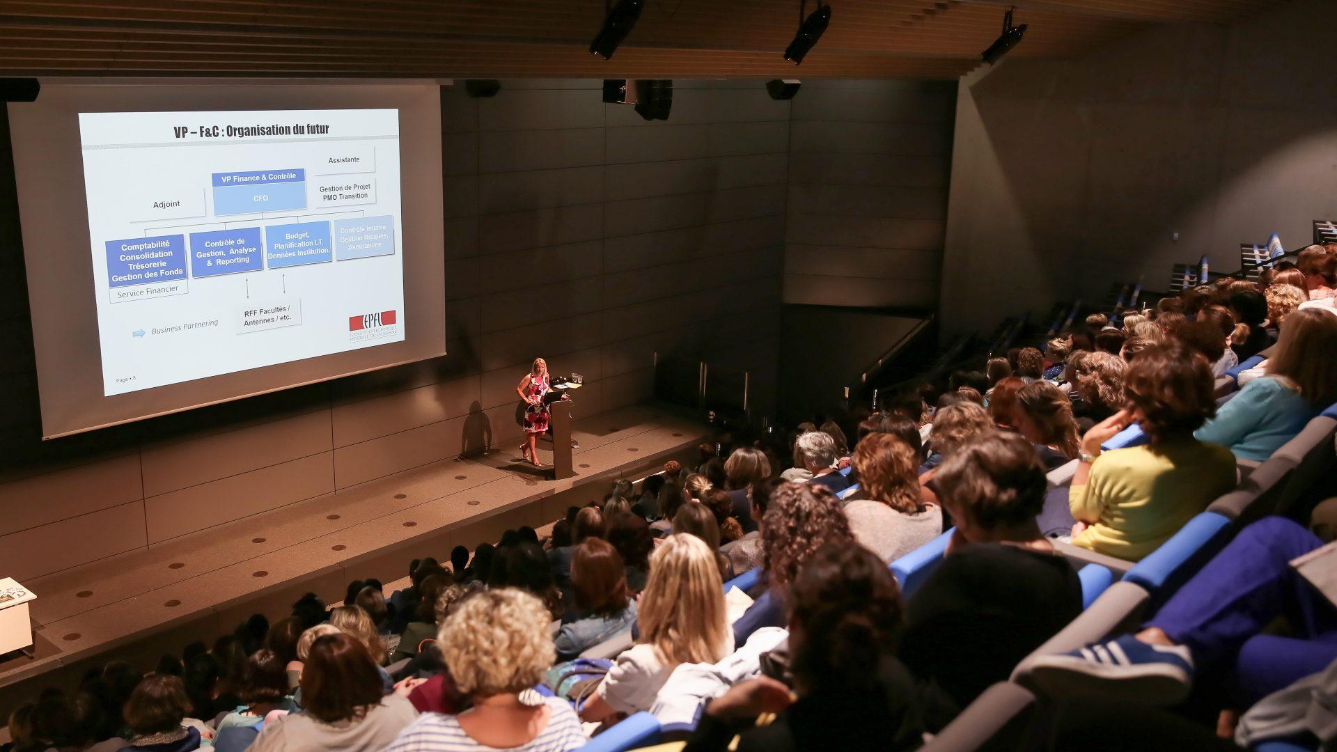 Dans un auditoire, la Vice-présidente Caroline Kuyper effectue une présentation. Sur un écran, une slide Powerpoint.