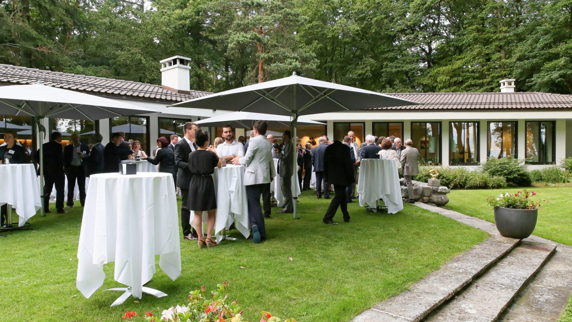 Des Alumni discutant autour d'une table, à l'extérieur d'un bâtiment, durant la Garden Party organisée en 2016.