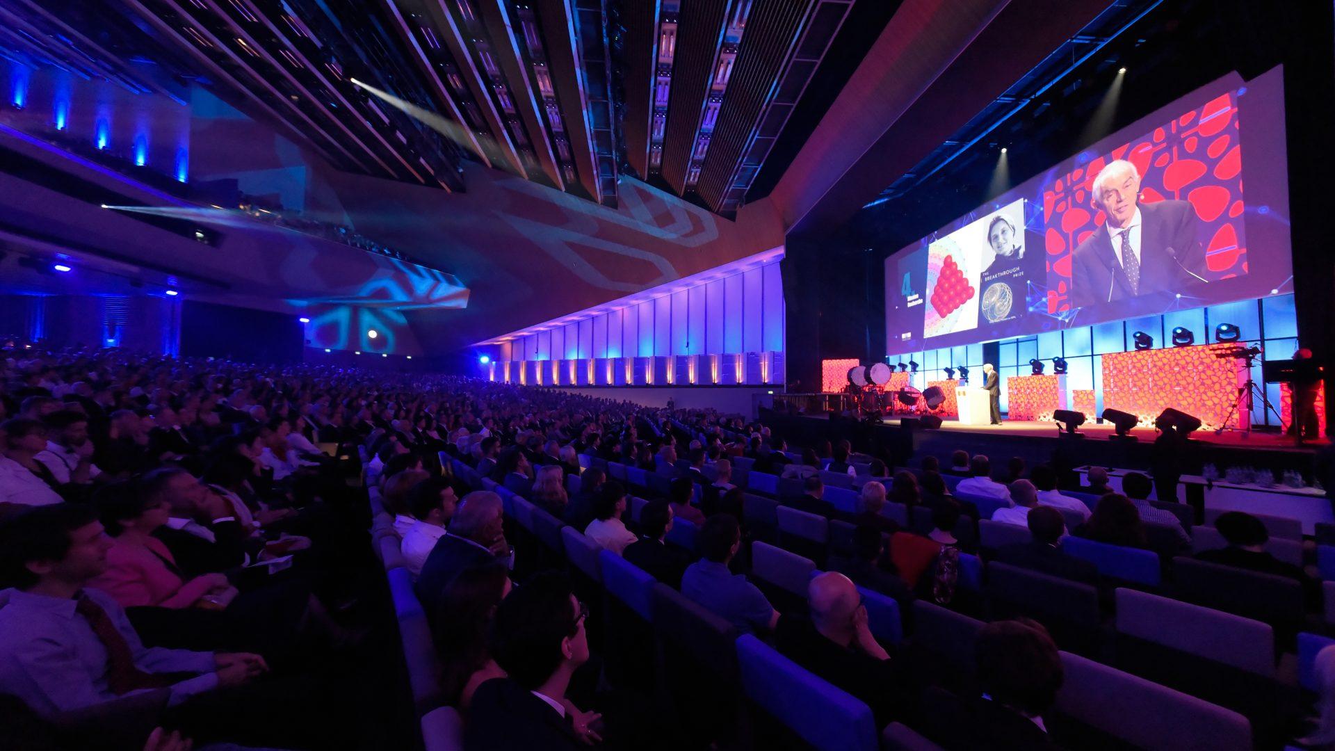 Vue du SwissTech Convention Center, plongé dans le noir. La salle est pleine. Sur la scène au second plan, Martin Vetterli donnant un discours. Au dessus de lui, des écrans retransmettant son discours.