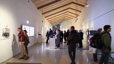 Intérieur du bâtiment ArtLab durant l'exposition Thinking Machines. Des visiteurs admirent les schémas affichés sur les murs.