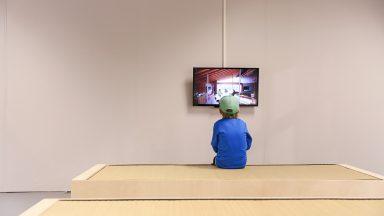 Un enfant, de dos, face à un écran dans ue grande salle vide d'Archizoom, durant la Nuit des Musées 2015