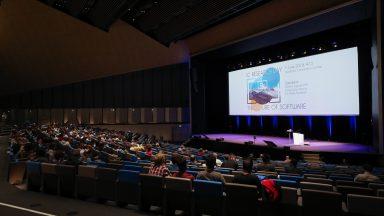 Intérieur du SwissTech Convention Center durant la ournée de la recherche IC. la salle est plongée dans le noir. Une présentation est en cours sur la scène.