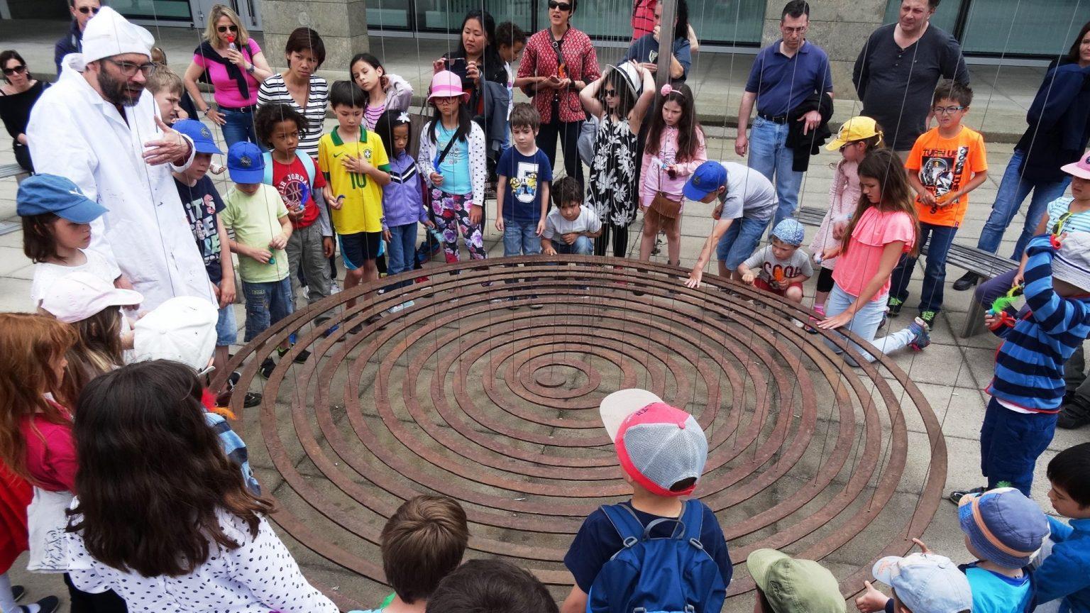 Des enfants autour d'une sculpture lors d'une promenade scientifique