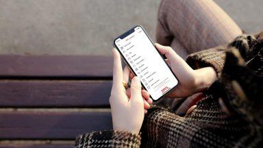 Une personne tenant dans ses mains un téléphone portable, avec l'application EPFL Campus