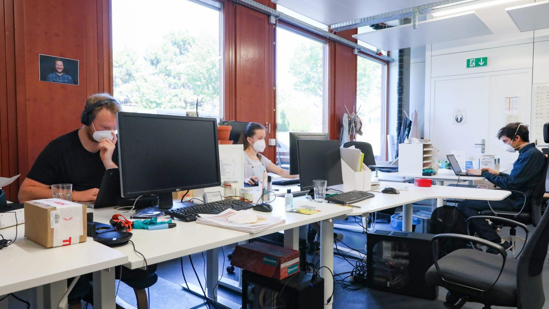 Des personnes travaillant sur des ordinateurs, avec des masques sur le visage