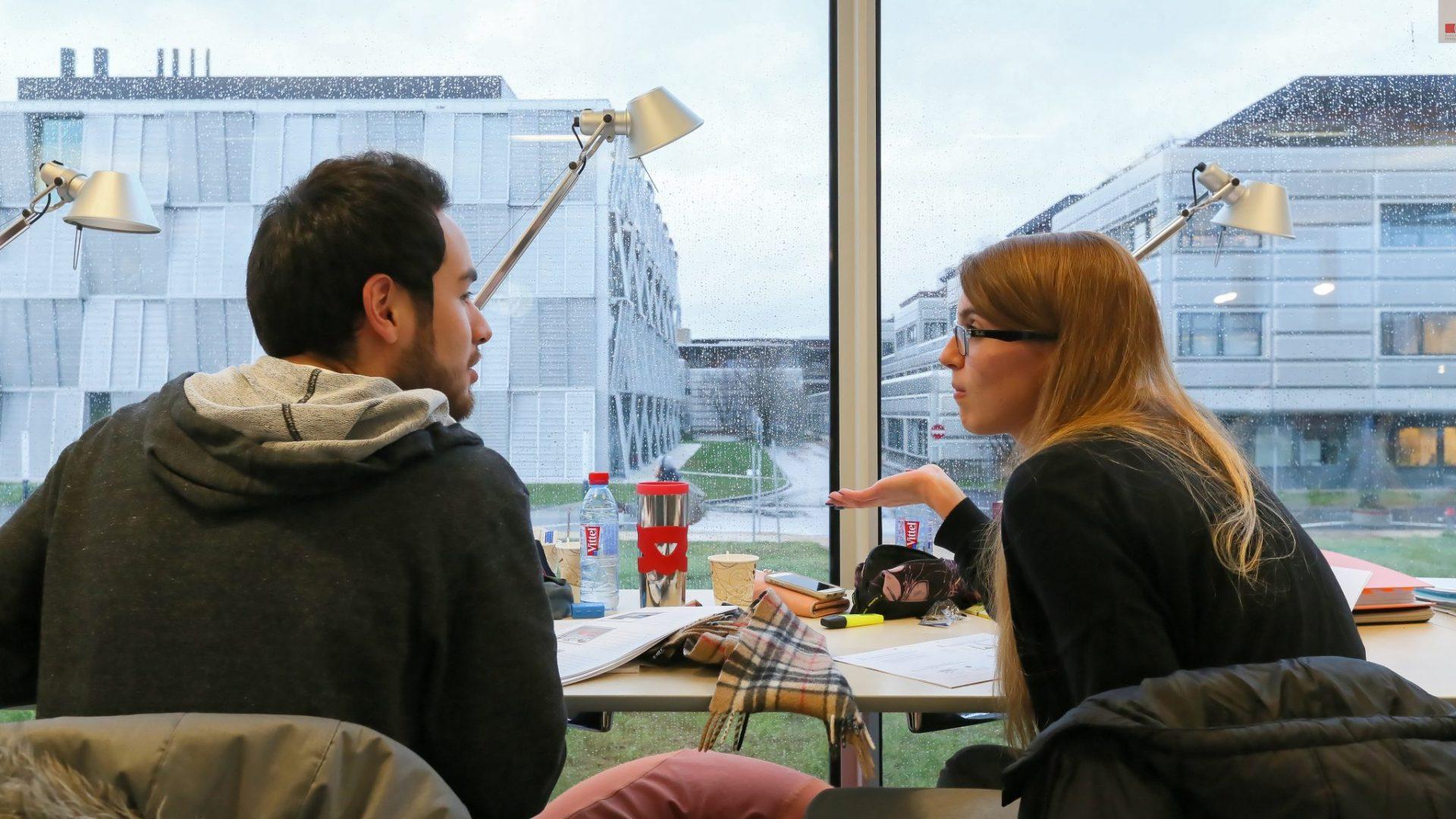 Des étudiants discutant devant une fenêtre du Rolex Learning Center, en révisant leurs examens