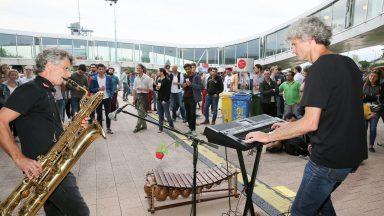 Deux personnes, au premier plan, jouant du saxophone et du piano électrique. Une foule les regardant au second plan
