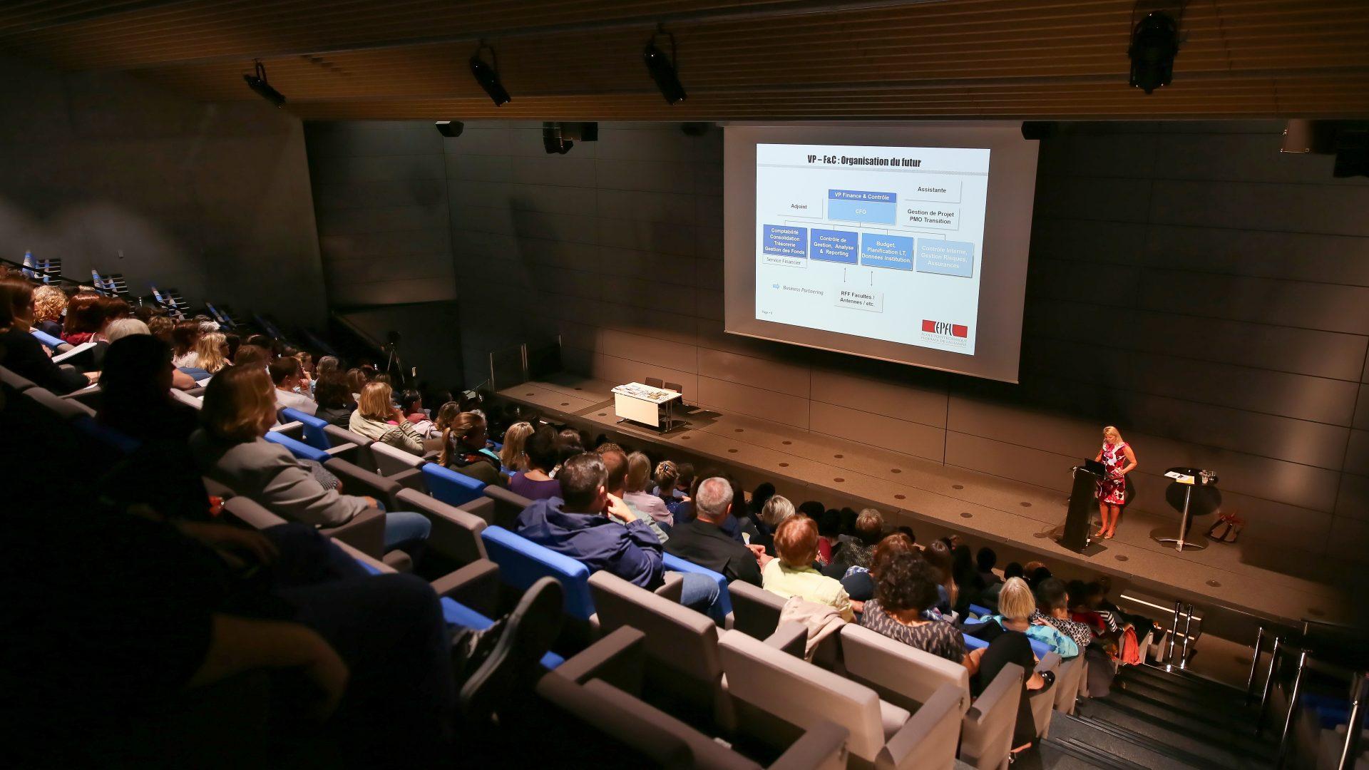 Un auditoire rempli avec, au second plan, une présentation Powerpoint