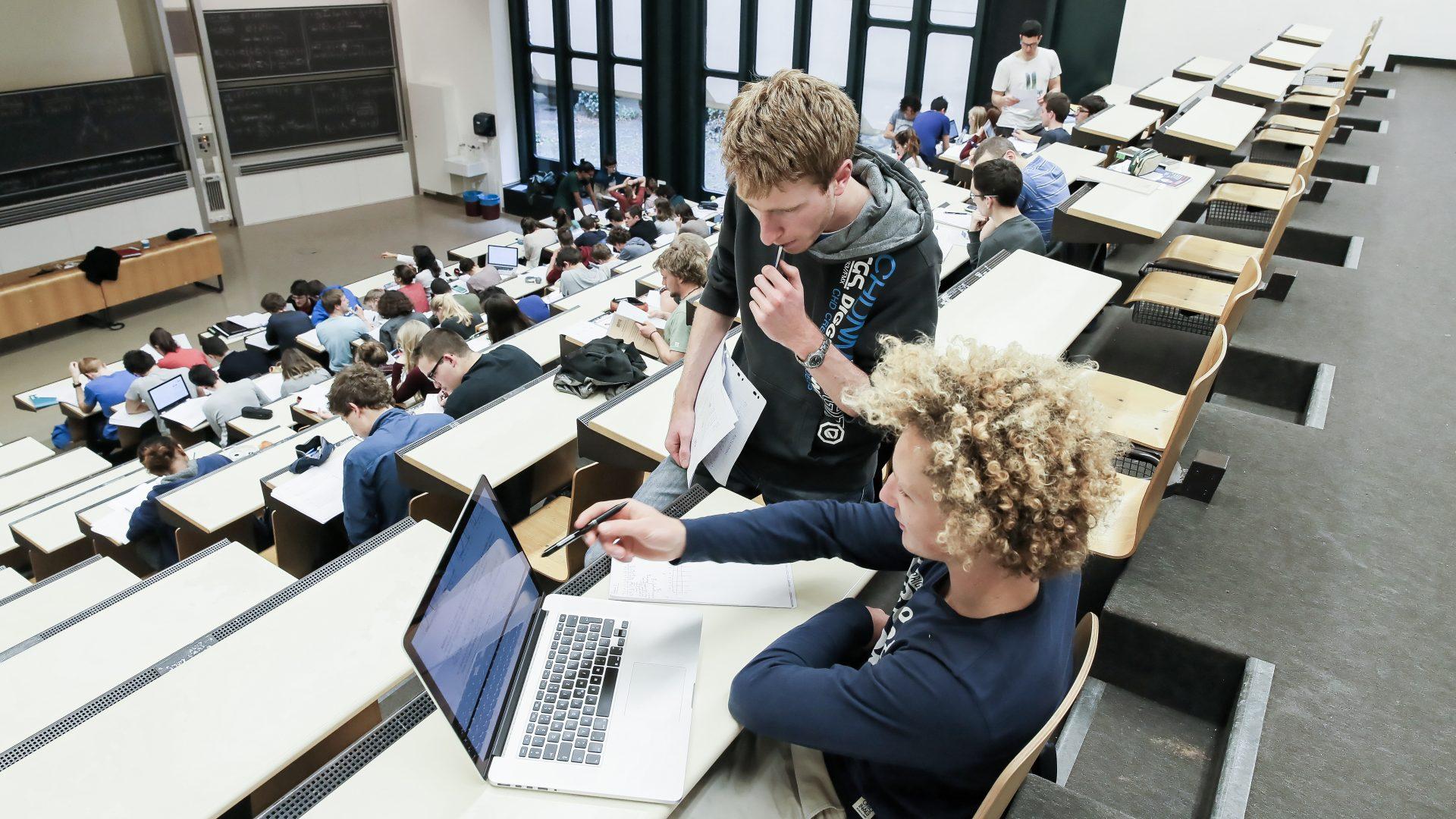 Vue sur un auditoire de l'EPFL, depuis le haut de la salle. Deux étudiants travaillant sur un ordinateur au premier plan.