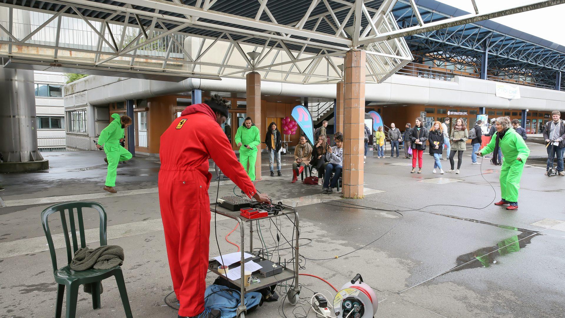 Sur l'Esplanade, une animation human beat-box et danse. Une personne, toute habillée de rouge au premier plan, fait du beat-boxing. Au secon plan, des danseurs tout habillés de vert.