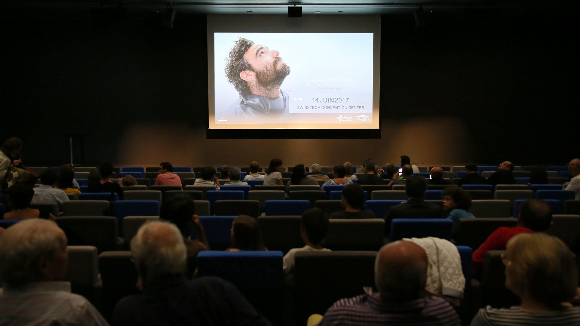 """Salle obscure, regardant, sur un écran """"L'aventure au bout du rêve"""" Le film du Vendée Globe d'Alan Roura"""