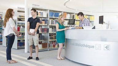 Des personnes au guichet de la bibliothèque du Rolex Learning Center.