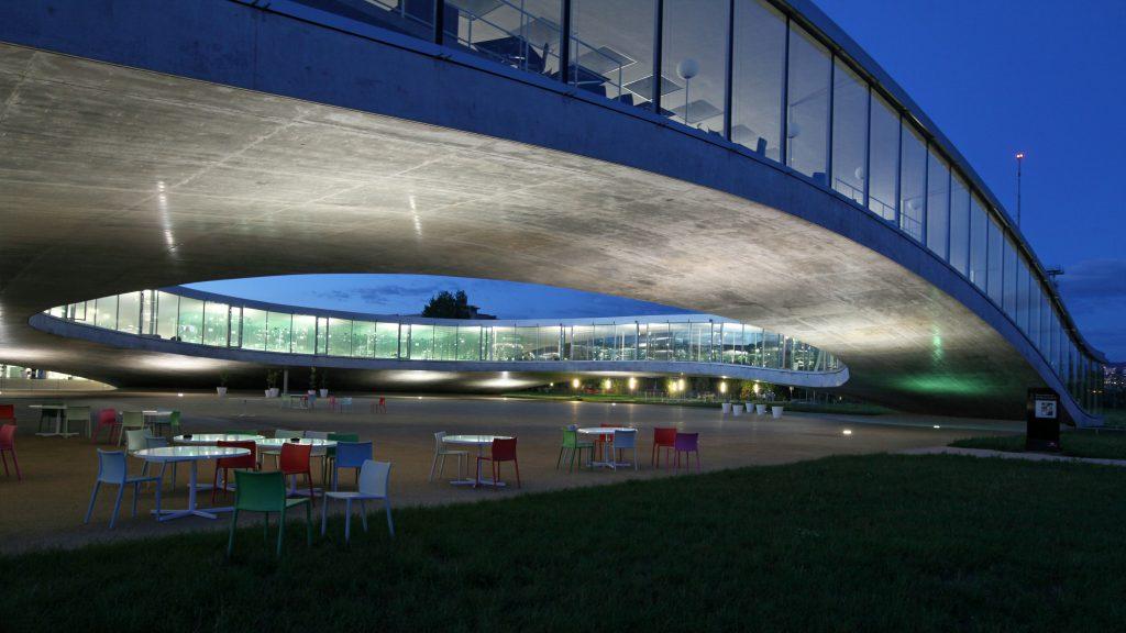 La cour intérieure du Rolex Learning Center, de nuit. Des chaises au premier plan
