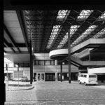 Photographie en noir et blanc de la toiture métallique en treillis tridimensionnels de l'école. Cette structure est portée par des poteaux en métal. La photo est prise au niveau de la rue. On voit sur la droite en arrière-plan les escaliers.