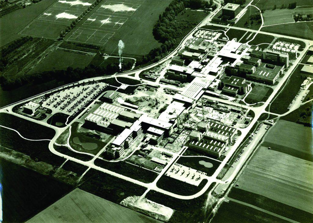 Photographie aérienne de l'EPFL. L'école est bordée par un paysage naturel (arbres, végétation).