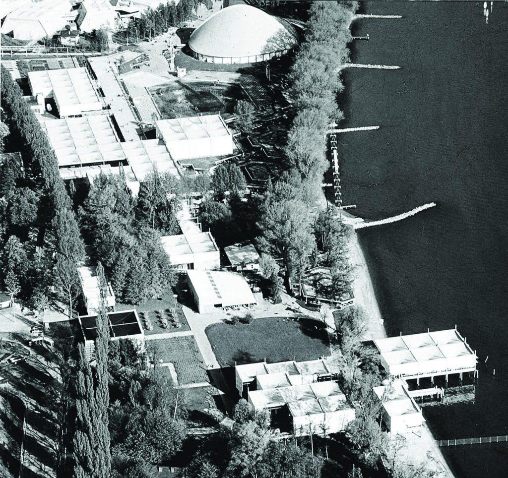 Photographie en noir et blanc depuis le ciel des pavillons réalisés pour l'exposition de Vidy. On observe la trame modulaire des bâtiments carrés juxtaposés les uns aux autres. Sur la droite le parc des expositions est bordé par le lac Léman. Il s'inscrit dans un paysage naturel, bordé d'arbres.