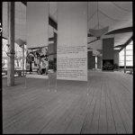 Exposition nationale suisse de 1964. Vue intérieure du pavillon du secteur Terre et forêt (architecte: Jakob Zweifel). Le plancher, les colonnes et les poutres sont en bois. Entre les poutres sont tendues des membranes en voile de coton.
