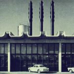 La photographie en noir et blanc est prise de manière frontale par rapport à la façade du centre agricole de Saint Aubin. La structure formée de poteaux et de poutres est en béton armé. Entre les poteaux, la façade est vitrée. La toiture est en béton armé. Elle est formée par la juxtaposition d'un module qui se répète à l'identique en forme de U.