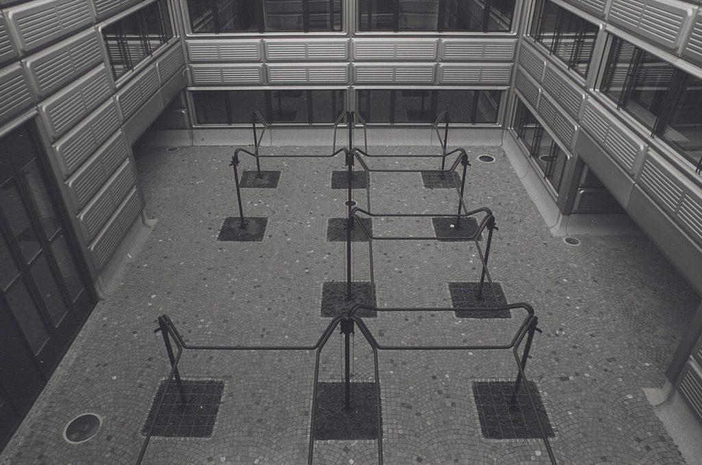 Photographie en noir et blanc d'une cour intérieure et des structures métalliques fixées dans le sol.