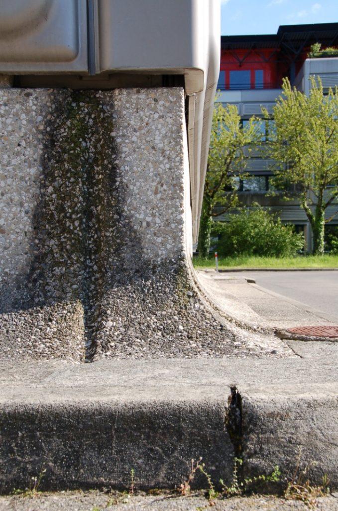 Détail d'un angle arrondi extérieur en béton au niveau du sol.