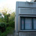 Vue sur un module couvert de panneaux métalliques au niveau du sol montrant la bordure arrondie du bâtiment, ancré dans le terrain.
