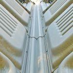 Détail d'un angle interne arrondi et des joints entre les panneaux d'aluminium.
