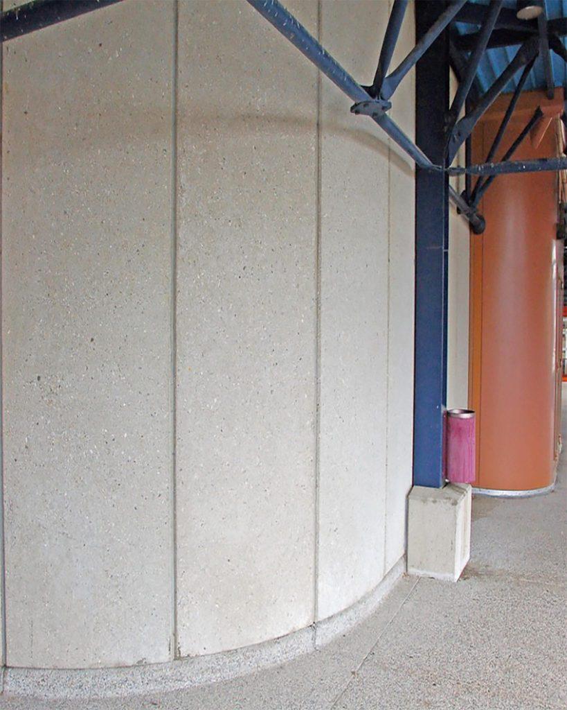 Façade colorée, au centre de la terrasse, formant une courbe, avec devant un pilier bleu.