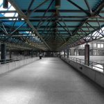 Vue sur la terrasse, au centre des bâtiments, entièrement grise, recouverte du treillis métallique bleu.