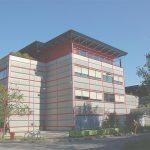 Extrémité d'un bâtiment revêtu de panneaux métalliques gris et couvert d'une structure métallique bleue, appartenant à la Faculté de Génie Civil, cadré en légère contre-plongée. Des lignes rouges quadrillent sa surface.