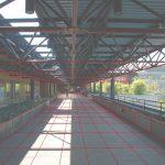 Vue de la terrasse, au sol pavé de dalles en béton granuleux, recouverte du treillis bleu métallique, du côté est, quadrillée de lignes rouges.