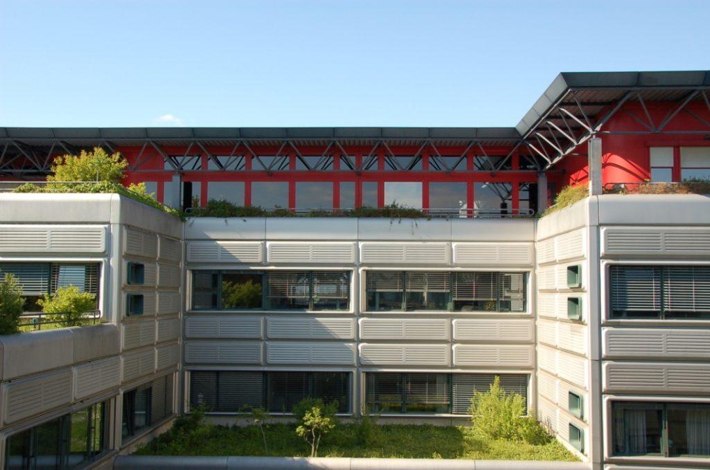 Détail d'un bâtiment de la Faculté de Génie Civil couvert en façade de panneaux métalliques gris qui alternent avec des fenêtres allongées et qui possèdent des avant-corps aux toits végétalisés. La toiture du bâtiment est faite d'une structure métallique bleue.