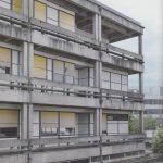 La façade en béton apparent trace une grille régulière faite d'éléments produits industriellement.
