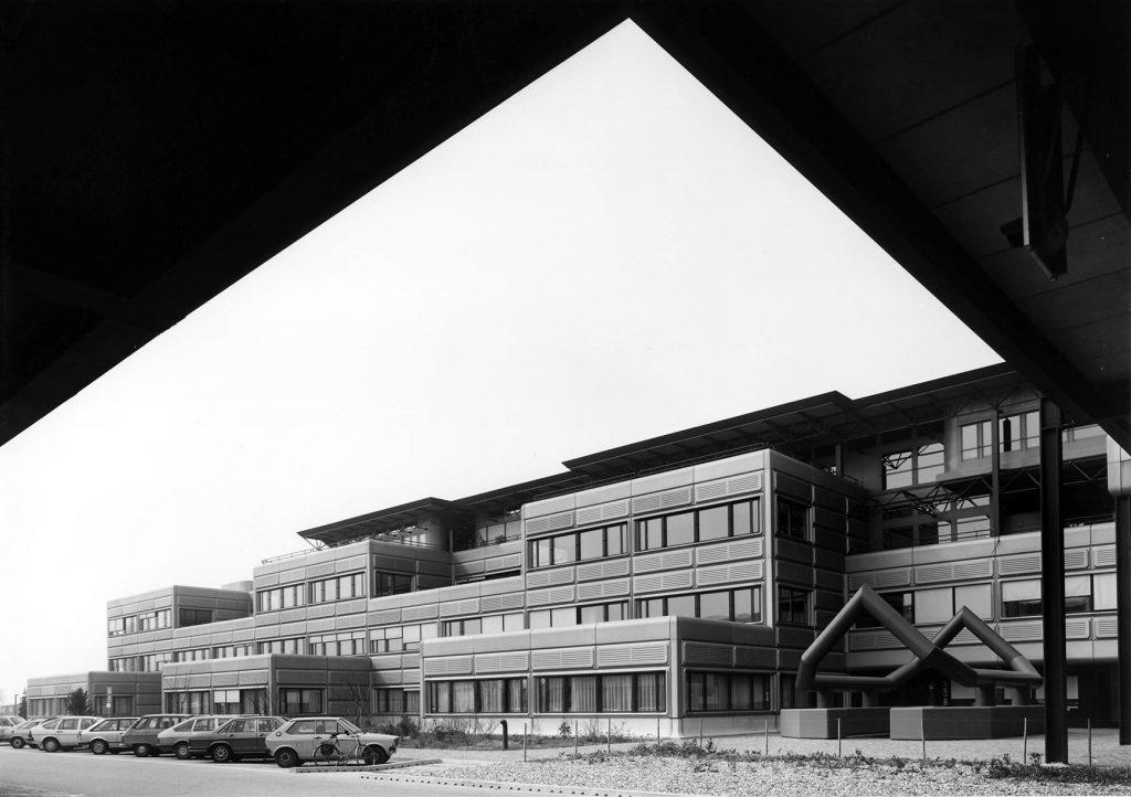 Photographie en noir et blanc prise sous la Méridienne à l'EPFL. Les façades sont revêtues de caissons métalliques arrondis aux angles.