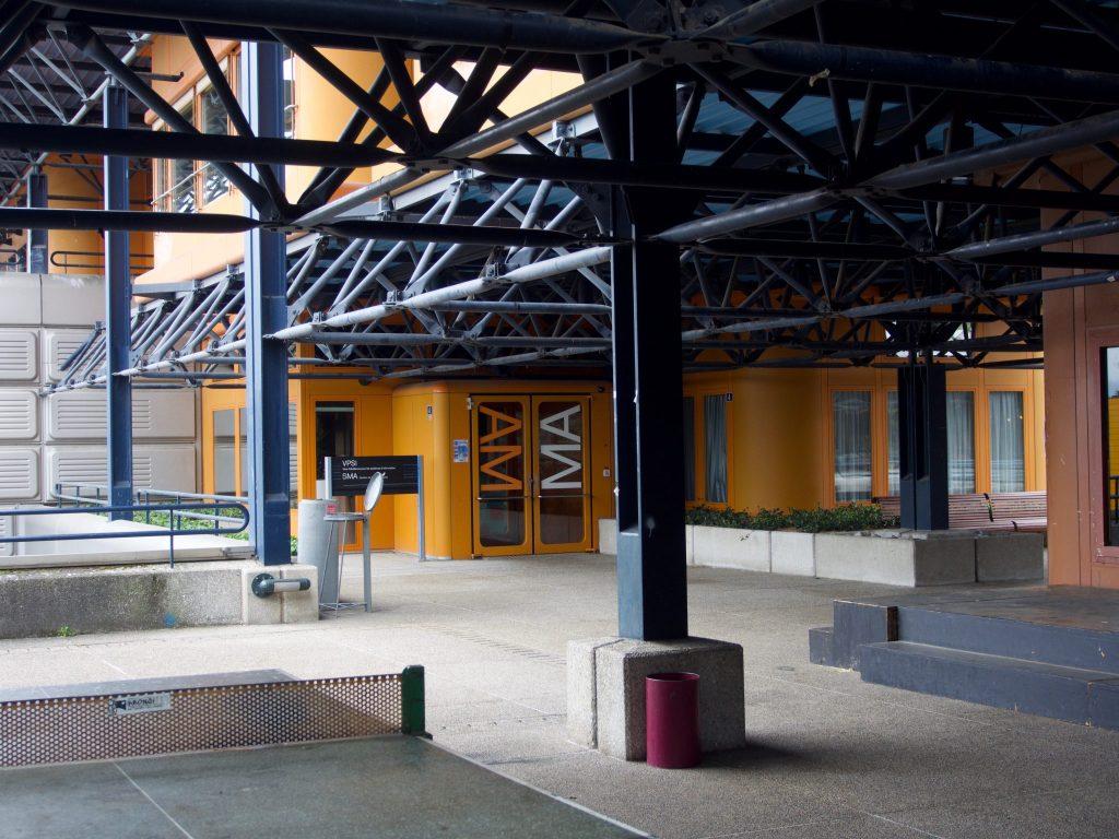 Sous la structure métallique bleue, la façade du bâtiment de la faculté de Mathématiques de l'EPFL affiche sa couleur orangée.