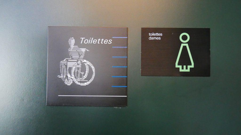 Photographie de deux panneaux différents pour indiquer les toilettes en 2019. Côte-à-côte, l'un date de l'époque Calame et l'autre de la période Ballmer.