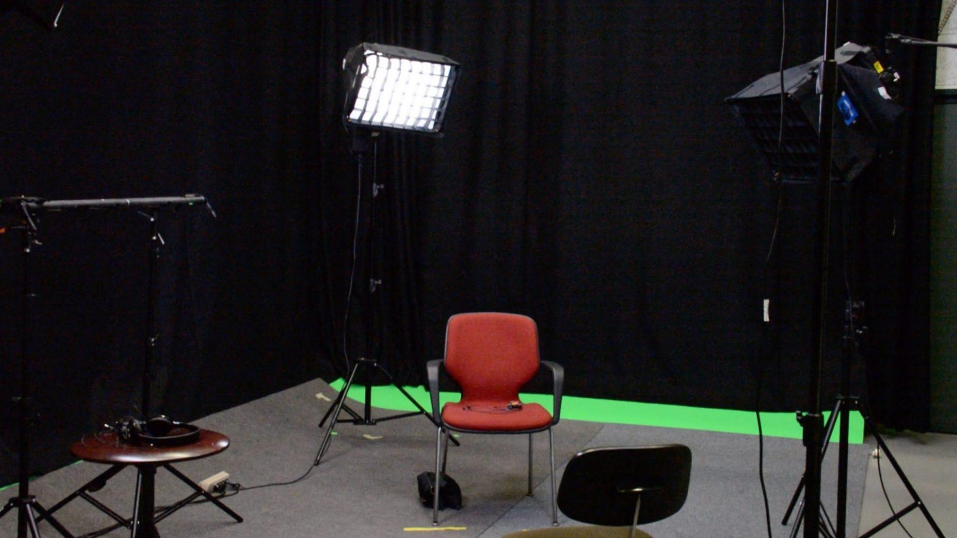 Vue du studio de télévision avec chaise, matériel d'éclairage, rideaux et fond vert.