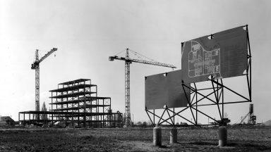 Vue du chantier de l'EPFL en avril 1975 montrant la structure des halles de chimie en construction, deux grues et deux panneaux de chantier au premier plan.