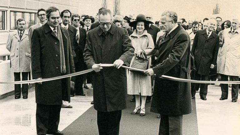 Un homme au centre de l'image coupe un ruban d'inauguration. Il est entouré de deux autres hommes se tenant sur le côté et d'une foule de personnes se tenant derrière lui.