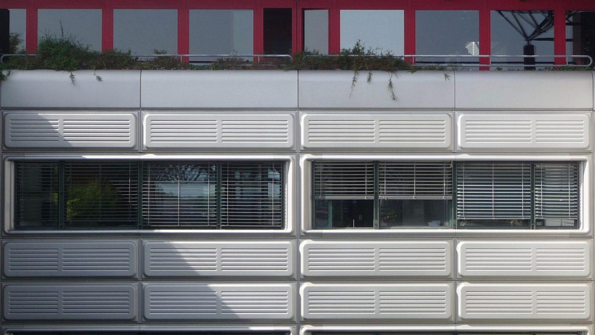 Vue d'une partie de la façade montrant au niveau inférieur quatre fenêtres disposées de manière symétrique entrecoupées verticalement de panneaux métalliques gris ; et au niveau supérieur la terrasse couverte d'un treillis bleu triangulaire et une façade rouge en retrait.