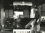 Vue sur un atelier dans lequel deux hommes soulèvent un panneau métallique hors d'une presse à emboutir, face à l'appareil photographique. Photographie en noir et blanc.